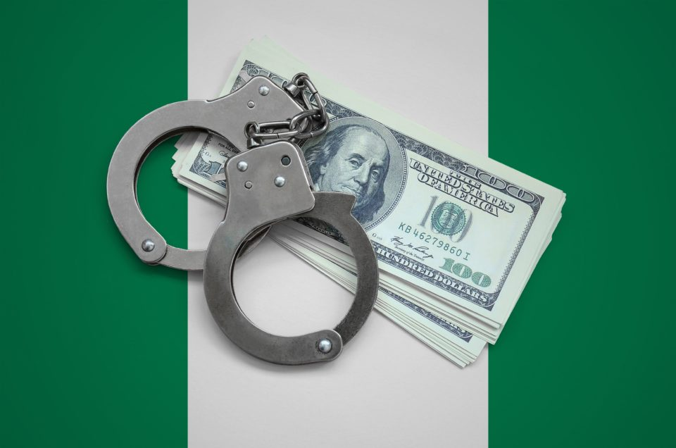 Barr. John Abba Scam Barr. John Abba Scam Nigeria flag with handcuffs and a bundle of dollars. Currency corruption in the country. Financial crimes