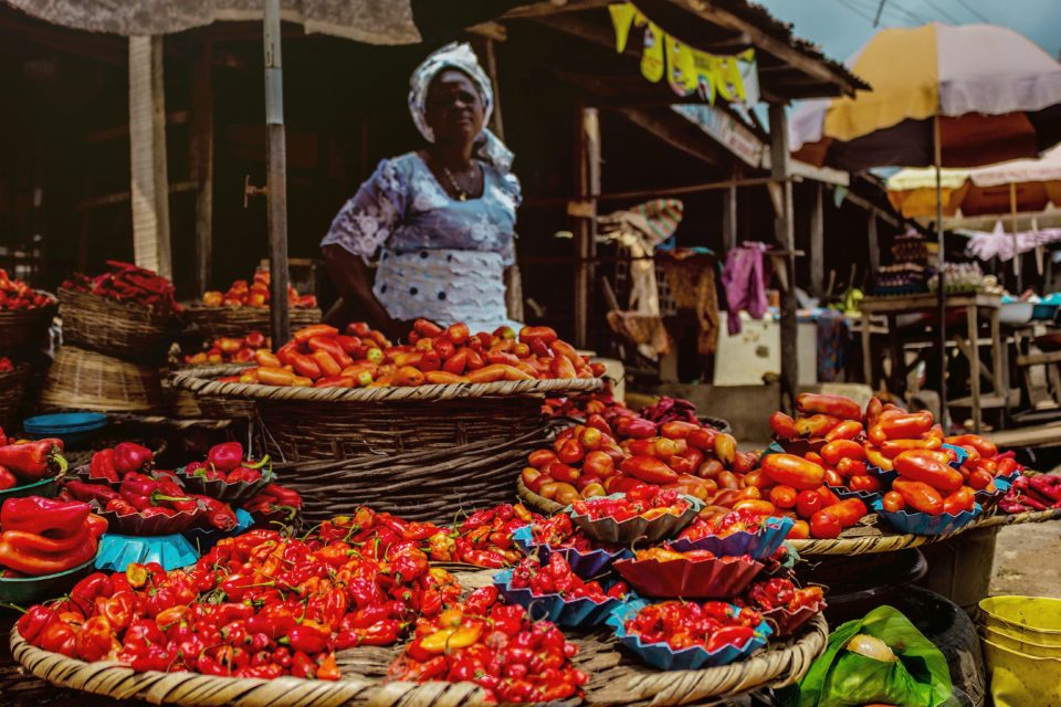 Woman selling pepper sits over her wares in a market.